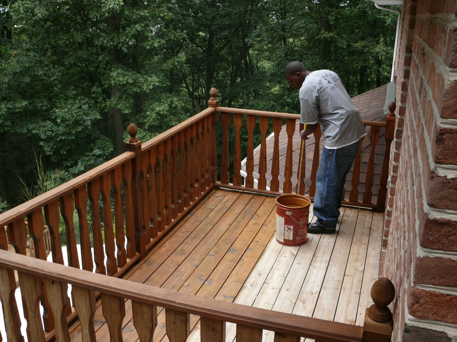 Deck staining by hand using a brush.