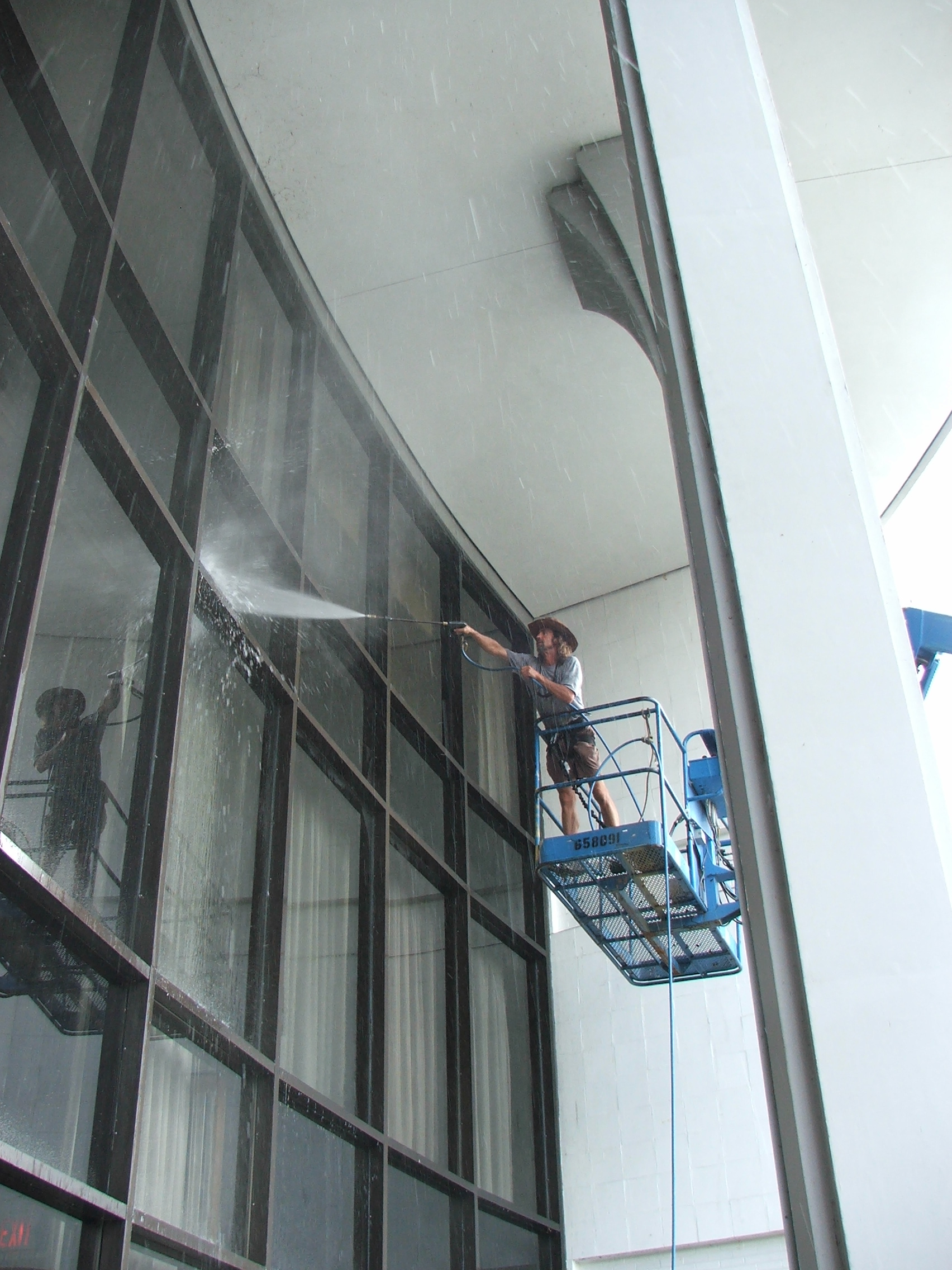 Pressure washing glass front entrance to remove dirt, cob webs and debris