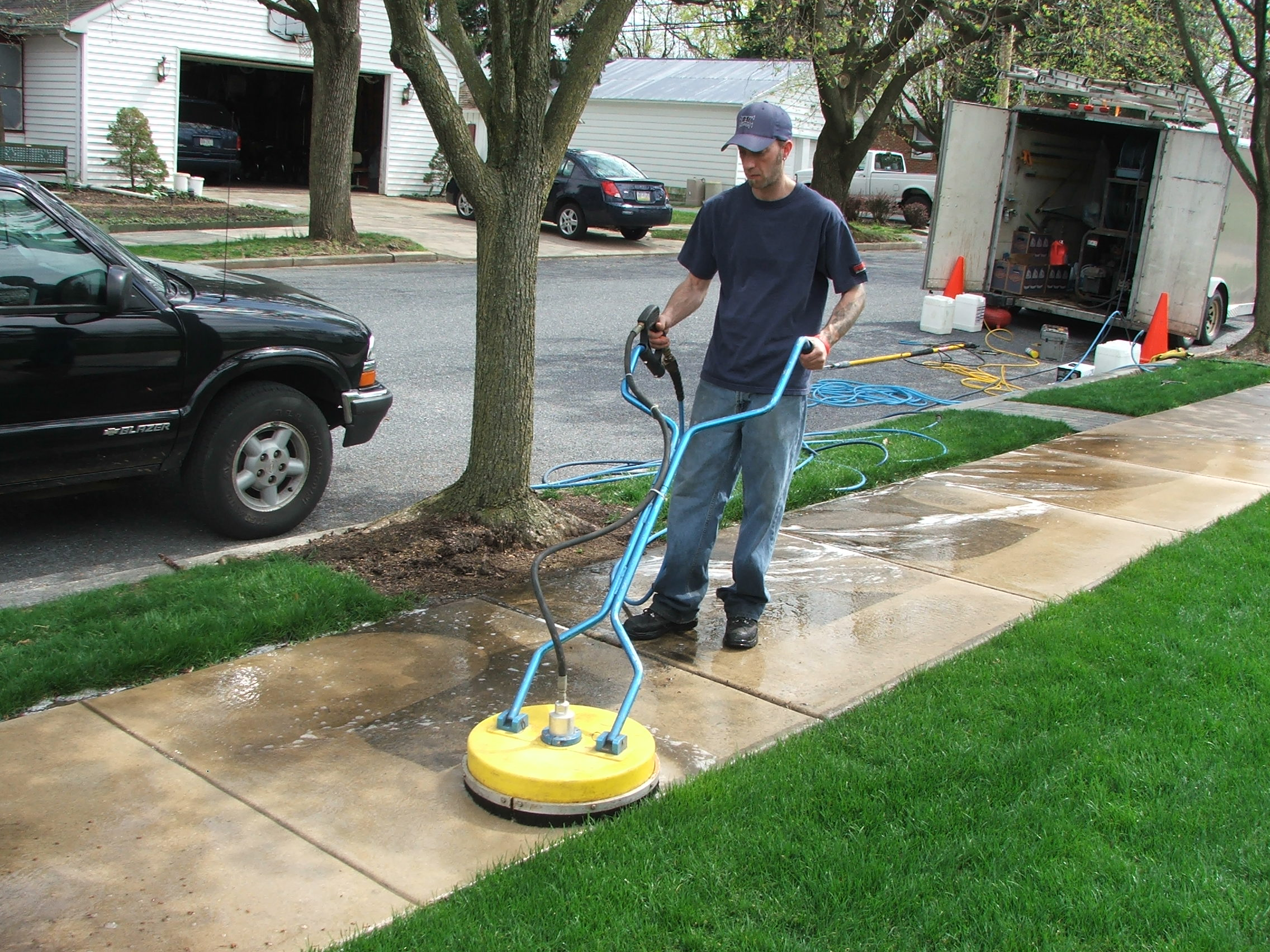 Pressure washing of sidewalks using a flat surface cleaning equipment.