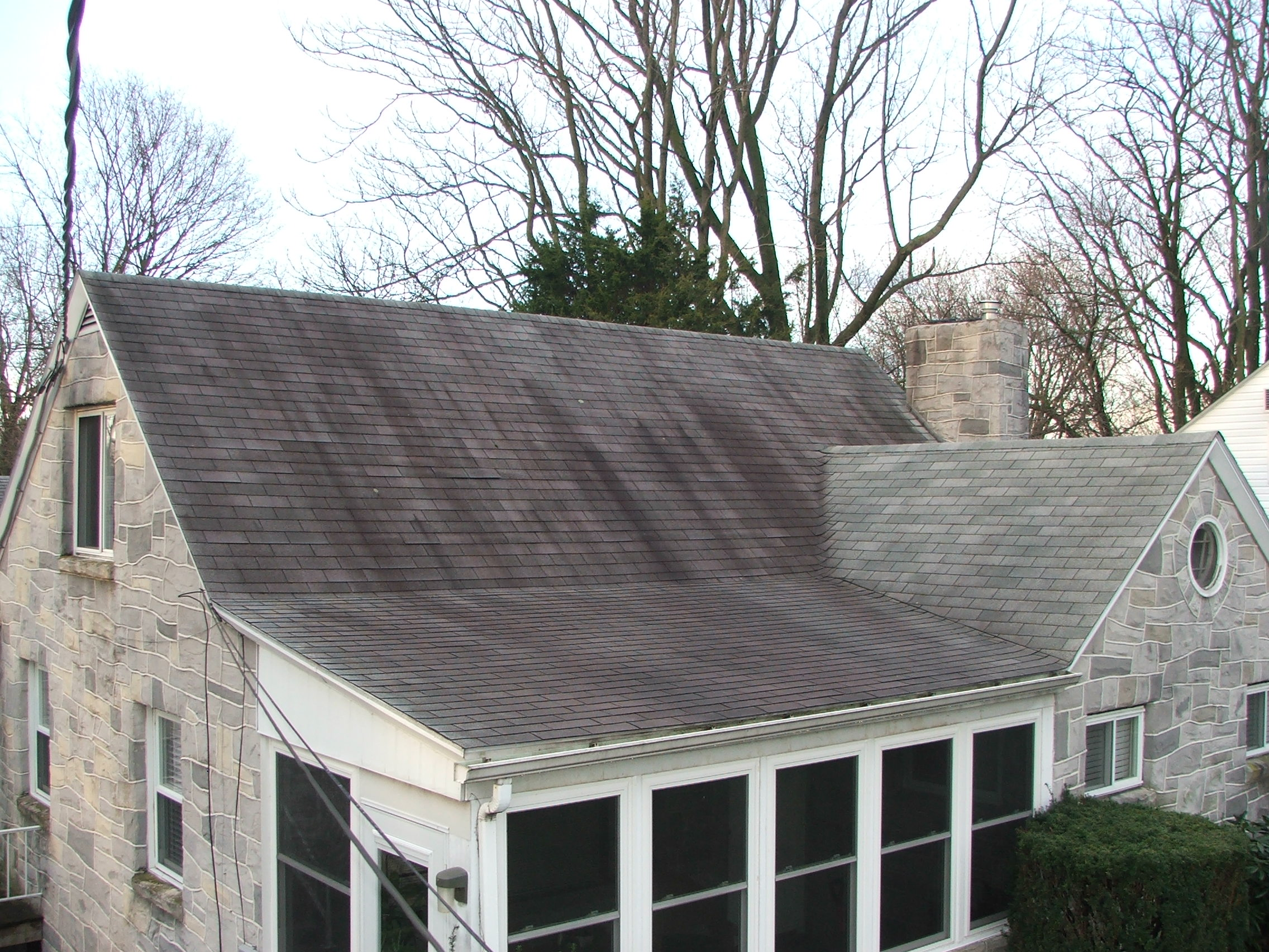 Dirty black stains on house roof before pressure washing
